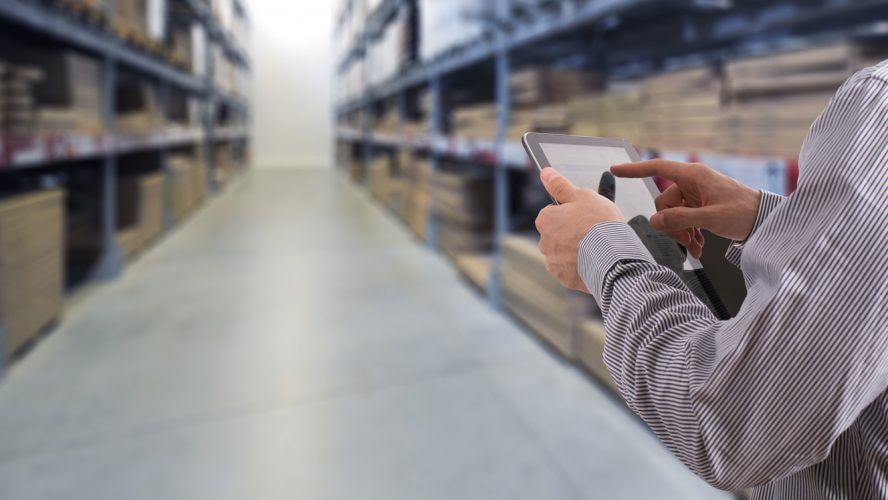 Businessman working on logistic inside stock room with touchscreen tablet.