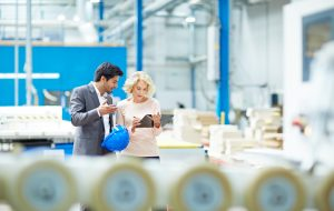 Young businessman reporting production details to senior female manager at factory shopfloor