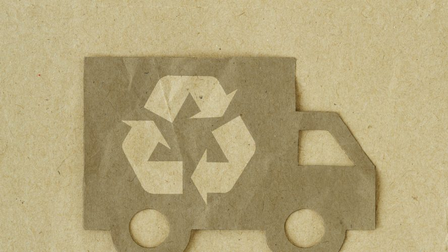 Paper cut of truck with recycling symbol on recycled paper background - Green transportation concept