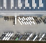 Aerial view of semi trucks during unloading and a large storehouse with solar panels on the rooftop.