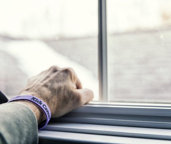"""A senior adult man cancer patient - about to start a three month chemotherapy regimen - is clenching his fist with his hand resting on a window sill - looking out toward the blurry and indistinct future outside the window. He is wearing a generic cancer themed wristband (personally """"designed"""" by me - the photographer/patient) with the embossed words """"Kick Cancer""""."""