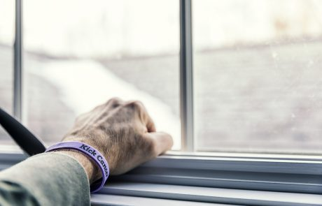 "A senior adult man cancer patient - about to start a three month chemotherapy regimen - is clenching his fist with his hand resting on a window sill - looking out toward the blurry and indistinct future outside the window. He is wearing a generic cancer themed wristband (personally ""designed"" by me - the photographer/patient) with the embossed words ""Kick Cancer""."