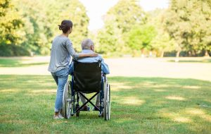 Caregiver and senior man on a wheelchair walking outdoors in a park