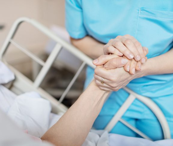 Midsection of female nurse holding senior woman's hand. Caring medical professional is with patient. She is consoling elderly woman in hospital.