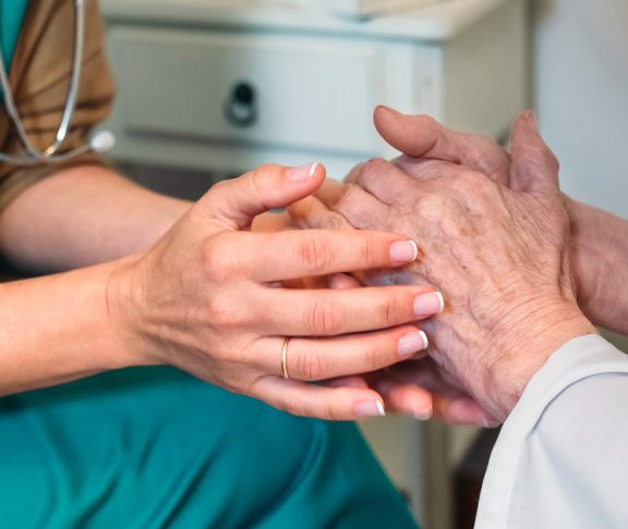 Female doctor giving encouragement to elderly patient by holding her hands