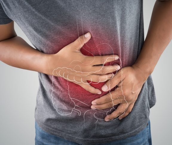 The photo of large intestine is on the man's body against gray background, People With Stomach ache problem concept, Male anatomy