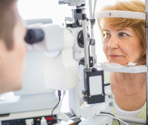Senior caucasian woman having her eyes examined at the optician.Her head is placed in phoropter apparatus while middle aged male doctor is examining her retina. The woman has mid length yellow brown hair and wearing light breen blouse.