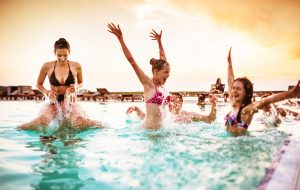 group of young adult girl having fun on swimming pool