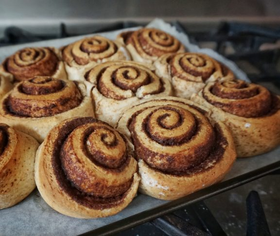 Fresh from the oven still on the baking pan homemade cooked from scratch cinnamon pastry buns baked breakfast food.