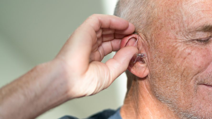 Senior male puts in hearing aid at the start of the day
