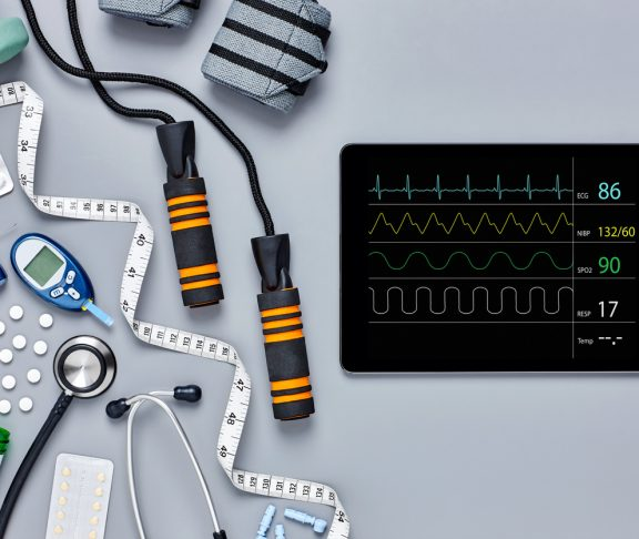 Directly above flat lay of medical equipment and digital tablet. Glucometer jump rope bandages and tape measure are diagonally placed with medicines. Computer screen is displaying pulse trace.
