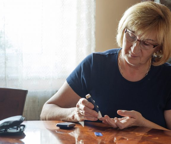 Senior woman in her 60s using sugar blood test to check the sugar level in blood stream. Woman is living life with chronic illness everyday and overcoming challenges that illness brings.