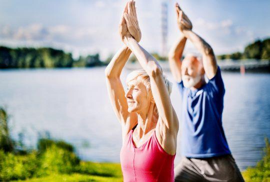 Mature couple in upward salute yoga pose outdoors. Side view. Horizontal.