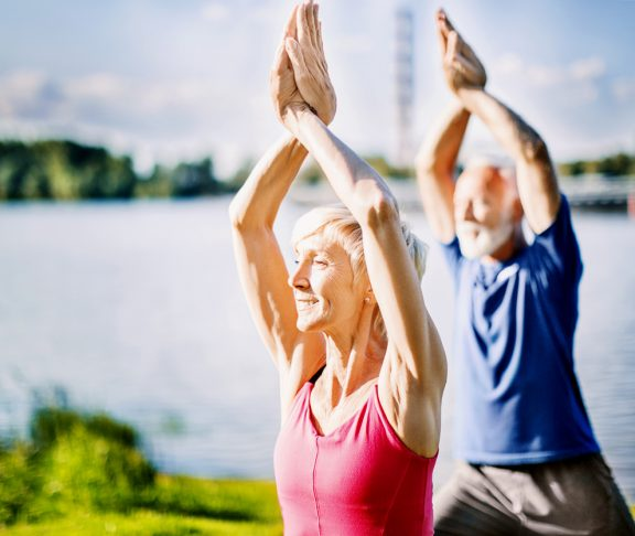 Mature couple in upward salute yoga pose outdoors. Side view. Horizontal.