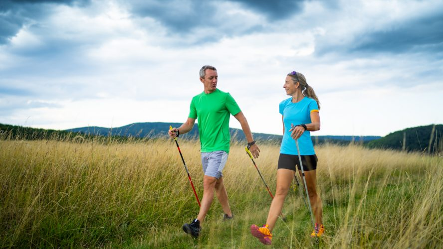 active smiling middle aged couple doing nordic walking sport in grassland with shallow focus cloudy overcast sky dark clouds front view