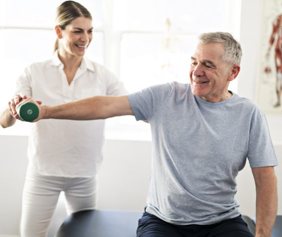 Modern rehabilitation physiotherapy worker with senior client
