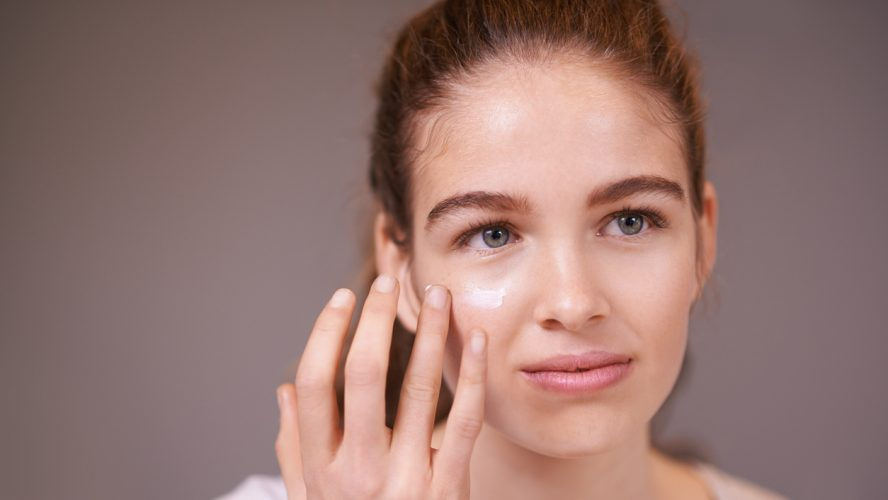 Shot of a teenager applying moisturizer to her