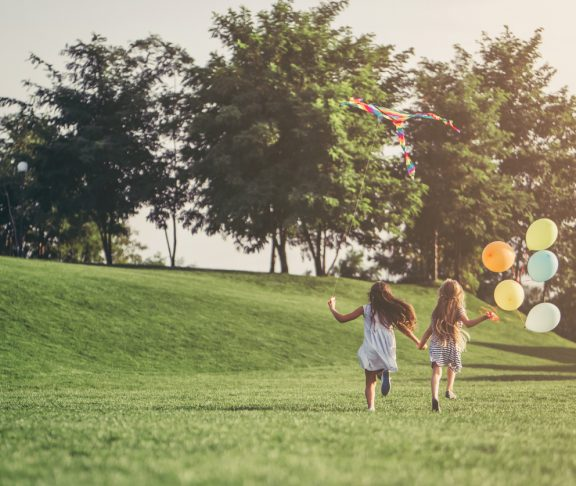 Little pretty girls having fun outdoor. Two cute girls are running on green grass with air balloons. Best friends