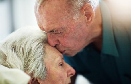 Cropped shot of a senior man kissing his sick wife on the forehead during a hospital visit