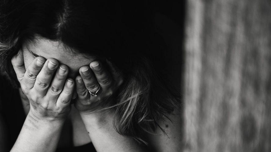Nainen pitelee päätään ja kärsii kovasta migreenistä