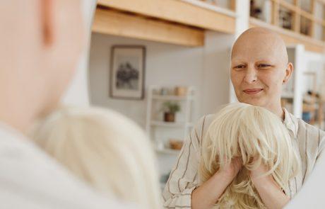 Syöpää sairastava nainen katsoo peiliin ja pitelee aidon näköistä peruukkia