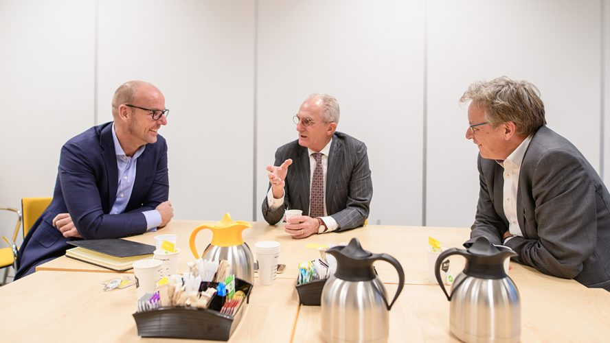 Drie mannen in gesprek aan een vergadertafel