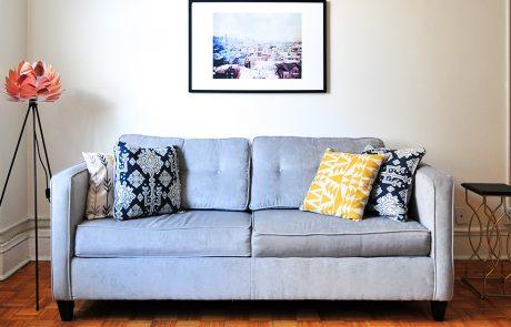 Gezellige woonkamer met grijze tweezitsbank, lamp en tafeltje