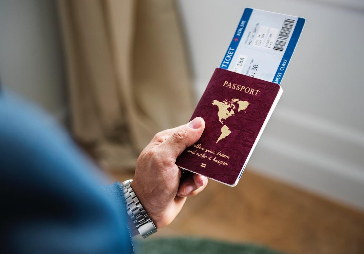 Persoon houdt paspoort en vlietguigticket vast