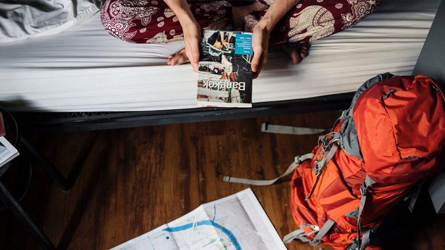 Reizen backpacker met reisgids en rugzak