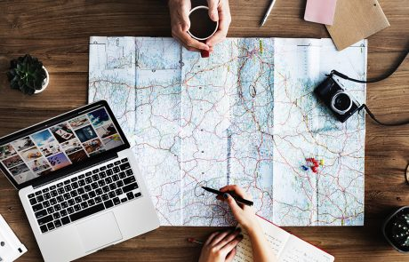 Twee personen plannen reis met landkaart en laptop op houten tafel