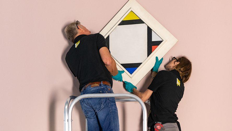 Twee personen hangen schilderij op