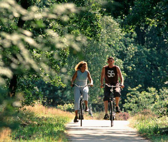 Twee personen fietsen door groen landschap