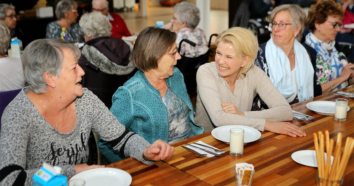 Anita Witzier aan tafel met andere mensen