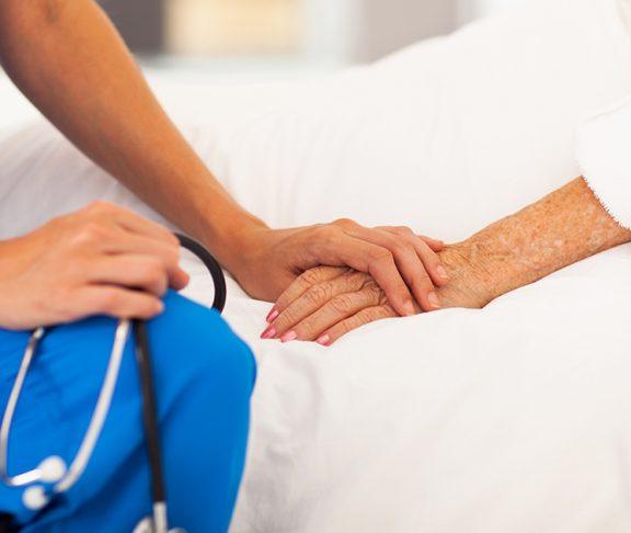 Dokter houdt hand vast van oude patiënt.