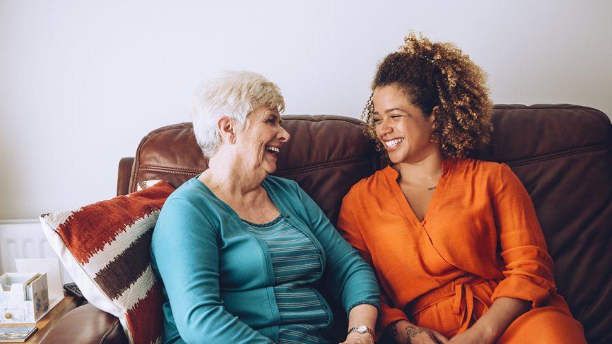 Oude en jonge vrouw zitten allebei op de bank