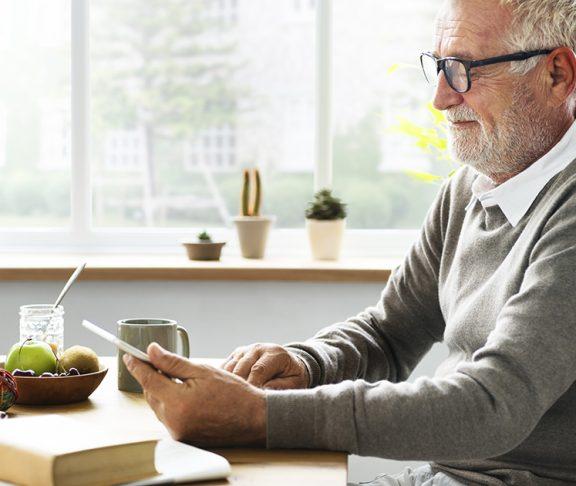 Oud man zit aan tafel met tablet.