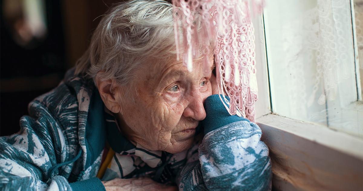 Oude eenzame vrouw zit bij het raam en kijkt naar buiten.