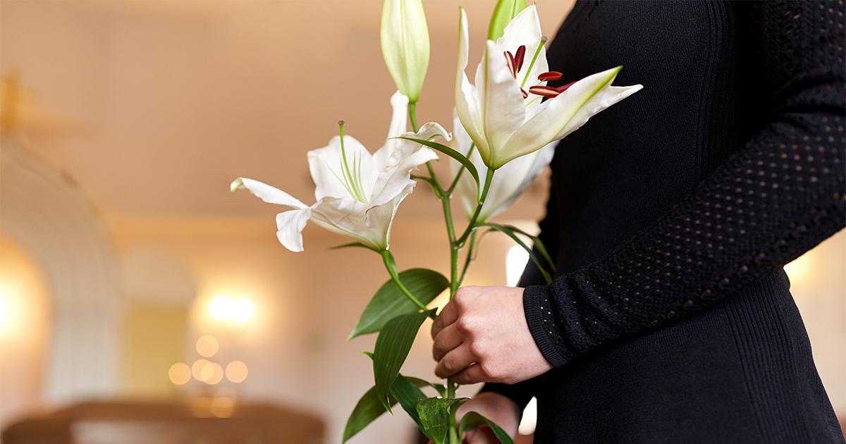 Vrouw in zwarte jurk met witte bloemen.