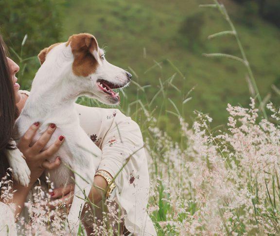 Jonge vrouw houdt hond vast, zit in groen heuvelachtig landschap.