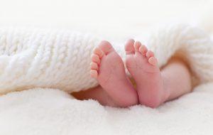Close-upfoto van babyvoetjes onder wit wollen deken.