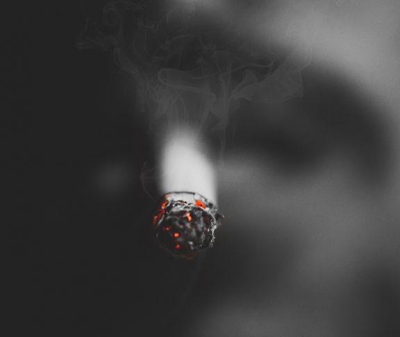 Close-upfoto van man met brandende sigaret