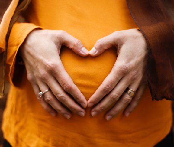 Zwangere vrouw legt handen op haar buik