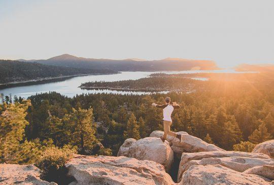 Avontuurlijke man springt op rotsen met zonsopgang aan de horzon.