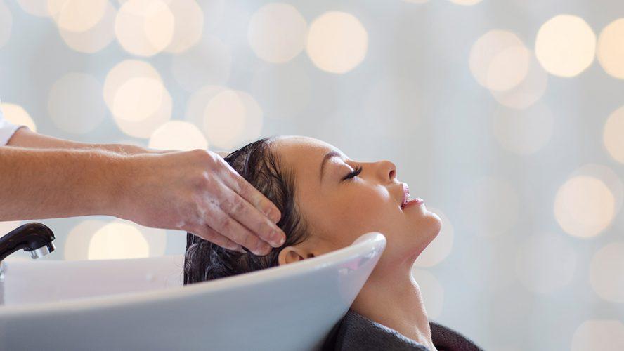 Kapper wast het haar van een jonge vrouw