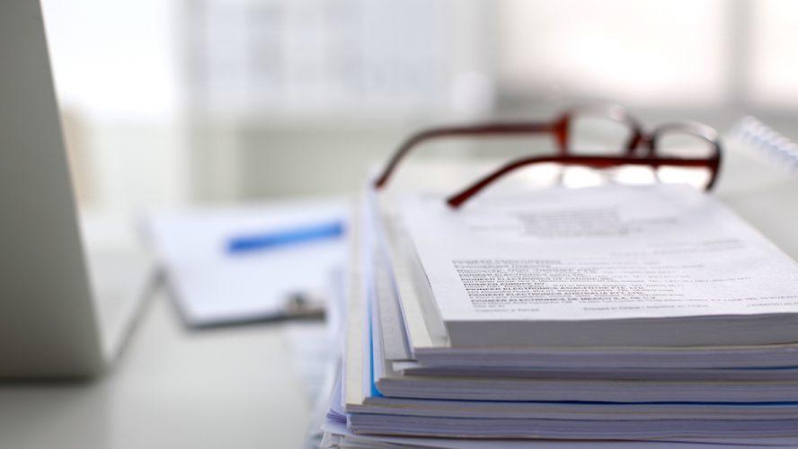 Foto selectieve focus van bril op stapel papieren.