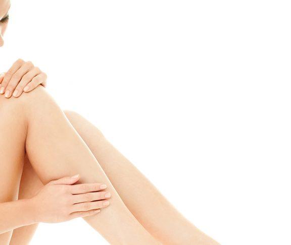 Jonge schaarsgeklede vrouw smeert huidcrème op haar benen.