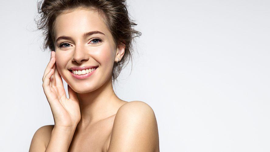 Jonge vrouw kijkt lachend in de camera.