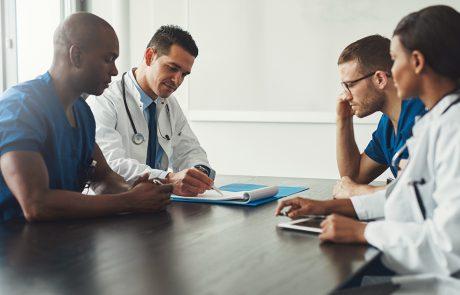 Vier dokters zitten samen in een meeting