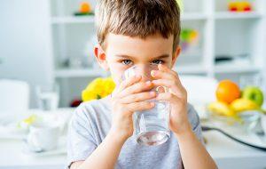Kleine jongen drinkt glas met water