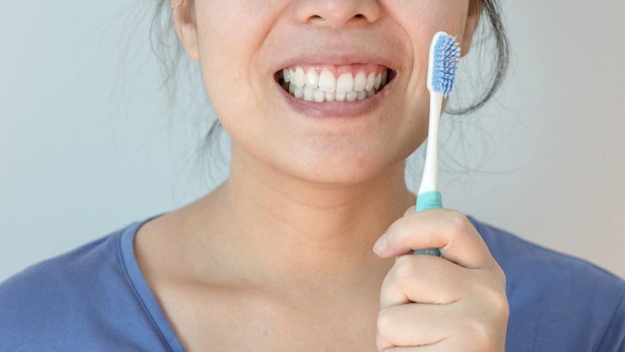 Vrouw toont tanden en tandenborstel